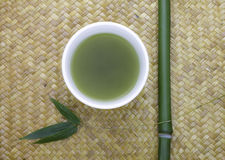 Schüssel des grünen Tees mit Bambus Stockfotografie