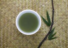 Schüssel des grünen Tees mit Bambusblättern Lizenzfreie Stockfotos