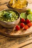 Schüssel des Guacamolebades mit Tortilla-Chip-Kalken und Kirschtomaten Lizenzfreie Stockfotografie