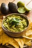 Schüssel des Guacamolebades mit Tortilla-Chips und Bestandteilen im Hintergrund Lizenzfreie Stockbilder
