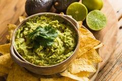 Schüssel des Guacamolebades und Tortilla-Chips mit Kalken und Avocados Lizenzfreies Stockfoto