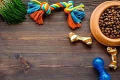 Schüssel, die mit trockenen Schoßhundlebensmittelstückchen und -spielwaren auf hölzernem Draufsichtmodell des Hintergrundes voll  Stockbilder