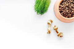 Schüssel, die mit trockenen Schoßhundlebensmittelstückchen und -spielwaren auf weißem Draufsichtmodell des Hintergrundes voll und Lizenzfreies Stockfoto