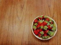 Schüssel Erdbeeren auf einem Holztisch: perfekter Hintergrund für Grüße lizenzfreie stockfotografie