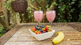 Schüssel Erdbeeren u. Beeren mit einer Banane und einer Erschütterung trinken Stockbild