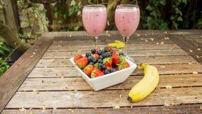 Schüssel Erdbeeren u. Beeren mit einer Banane und einer Erschütterung trinken Stockfoto