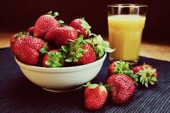 Schüssel Erdbeeren u. Orangensaft-Glas Lizenzfreies Stockbild
