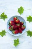 Schüssel frische Erdbeeren auf der weißen Tabelle mit grünen Blättern Stockfotos