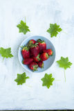 Schüssel frische Erdbeeren auf der weißen Tabelle mit grünen Blättern Stockfotografie