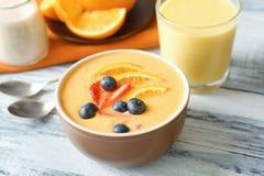 Schüssel frischen Jogurt Smoothie mit Orange und Beeren Lizenzfreie Stockfotos