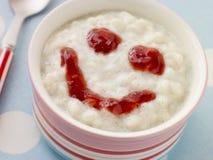 Schüssel gesahnter Reis-Pudding mit einer Erdbeere Stockfoto
