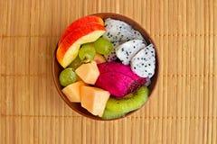 Schüssel gesunder frischer Obstsalat auf hölzernem Hintergrund Stockbilder