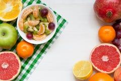 Schüssel gesunder frischer Obstsalat auf weißem hölzernem Hintergrund, Draufsicht, Kopienraum lizenzfreie stockfotografie