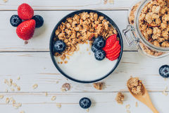 Schüssel Granola mit Jogurt, frische Beeren, Erdbeere auf Holz t Lizenzfreies Stockbild