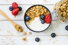 Schüssel Granola mit Jogurt, frische Beeren, Erdbeere auf Holz t Stockfotografie