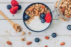 Schüssel Granola mit Jogurt, frischen Beeren, Blaubeeren und Nuss Lizenzfreie Stockbilder