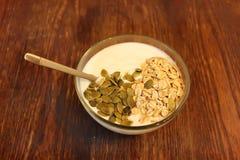 Schüssel griechischer Jogurt mit Hafermehl und Samen auf Holztisch Lizenzfreie Stockbilder