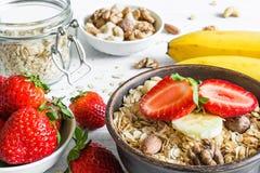Schüssel Hafer muesli mit Erdbeere, Banane, Granola und Nüssen Lizenzfreie Stockbilder