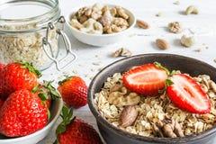 Schüssel Hafer muesli mit Erdbeere, Granola und Nüssen auf rustikalem w Stockfoto