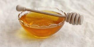 Schüssel Honig mit hölzernem drizzler Lizenzfreie Stockbilder