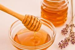 Schüssel Honig mit hölzernem Schöpflöffel drizzler Stockfotografie