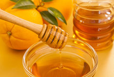 Schüssel Honig mit hölzernem Schöpflöffeldrizzler und -orangen Stockfotos