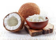 Schüssel Kokosnussöl und frische Kokosnüsse lizenzfreie stockbilder