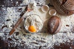 Schüssel Mehl mit Ei und Brot stockbild