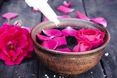 Schüssel mit den roten rosafarbenen Blumenblättern auf einem Hintergrund von dunklen hölzernen Brettern und von ätherischem Öl mi stockbild