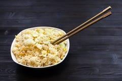 Schüssel mit Fried Rice mit Essstäbchen auf dunkler Tabelle stockbilder