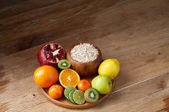 Schüssel mit Hafermehlflocken diente mit Früchten auf hölzernem Behälter über rustikalem Hintergrund, flach Lage, selektiver Foku Lizenzfreie Stockbilder