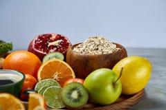 Schüssel mit Hafermehlflocken diente mit Früchten auf hölzernem Behälter über rustikalem Hintergrund, flach Lage, selektiver Foku Stockfotografie