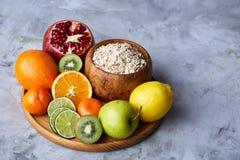 Schüssel mit Hafermehlflocken diente mit Früchten auf hölzernem Behälter über rustikalem Hintergrund, flach Lage, selektiver Foku Lizenzfreie Stockfotografie