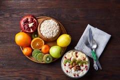 Schüssel mit Hafermehlflocken diente mit Früchten auf hölzernem Behälter über rustikalem Hintergrund, flach Lage, selektiver Foku Lizenzfreies Stockfoto