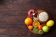 Schüssel mit Hafermehlflocken diente mit Früchten auf hölzernem Behälter über rustikalem Hintergrund, flach Lage, selektiver Foku Stockfotos