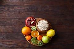Schüssel mit Hafermehlflocken diente mit Früchten auf hölzernem Behälter über rustikalem Hintergrund, flach Lage, selektiver Foku Lizenzfreies Stockbild