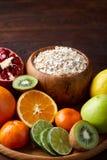 Schüssel mit Hafermehlflocken diente mit Früchten auf hölzernem Behälter über rustikalem Hintergrund, flach Lage, selektiver Foku Stockbild