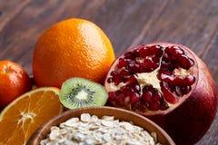 Schüssel mit Hafermehlflocken diente mit Früchten auf hölzernem Behälter über rustikalem Hintergrund, flach Lage, selektiver Foku Lizenzfreie Stockfotos