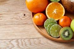 Schüssel mit Hafermehlflocken diente mit Früchten auf hölzernem Behälter über rustikalem Hintergrund, flach Lage, selektiver Foku Stockfoto