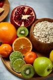 Schüssel mit Hafermehlflocken diente mit Früchten auf weißem Hintergrund des hölzernen Behälters, flach Lage, selektiver Fokus Stockbilder