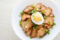 Schüssel Reis überstiegen mit dem gedünsteten Schweinebauch stockbild