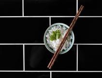 Schüssel Reis auf schwarzem mit Ziegeln gedecktem Hintergrund von den Unkosten stockfotografie