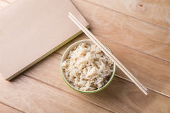 Schüssel Reis mit hölzernen Essstäbchen auf dem Tisch. Lizenzfreies Stockbild