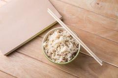 Schüssel Reis mit hölzernen Essstäbchen auf dem Tisch. Lizenzfreie Stockbilder