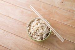 Schüssel Reis mit hölzernen Essstäbchen auf dem Tisch. Lizenzfreie Stockfotos