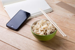Schüssel Reis mit hölzernen Essstäbchen auf dem Tisch. Stockfotos