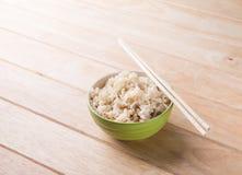 Schüssel Reis mit hölzernen Essstäbchen auf dem Tisch. Stockfoto