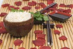 Schüssel Reis mit orientalischen Steuerknüppeln über Bambus Lizenzfreies Stockfoto