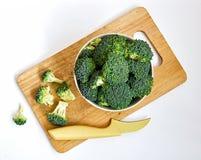 Schüssel rohe Brokkolisprösslinge auf Schneidebrett lizenzfreie stockfotografie