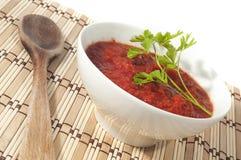Schüssel Tomatensauce auf hölzerner Steuerknüppeltischdecke Stockfotos